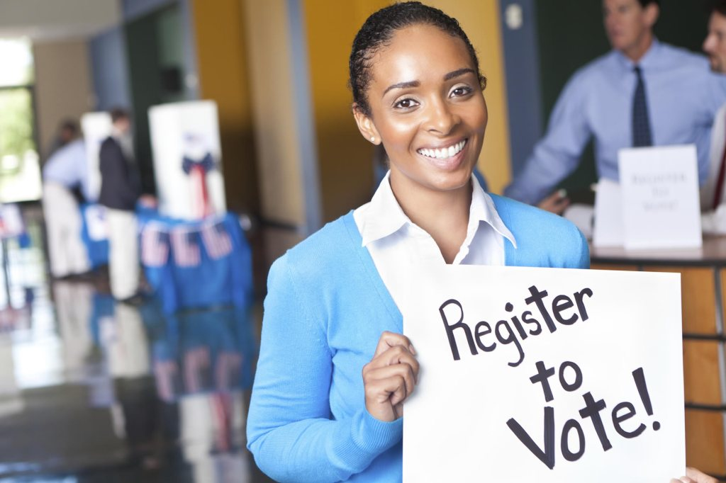 Woman holding sign that says Register To Vote!